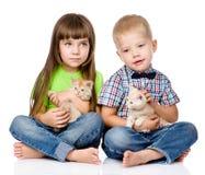 Ragazzino e ragazza che abbracciano gattino Isolato su priorità bassa bianca Fotografia Stock