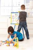 Ragazzino e ragazza che giocano al tavolo da disegno Fotografia Stock Libera da Diritti