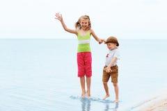 Ragazzino e ragazza che saltano e che si divertono Emozioni positive Fotografia Stock