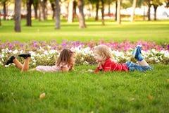 Ragazzino e ragazza che si trovano sull'erba Fotografia Stock