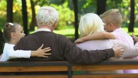Ragazzino e ragazza che vengono ai nonni che si siedono sul banco in parco, giorno della famiglia stock footage