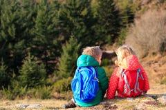 Ragazzino e ragazza con gli zainhi che hanno resto in montagne Fotografia Stock