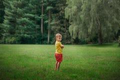 Ragazzino ed esaminare macchina fotografica sulla natura il ragazzo guarda hurtly sopra la sua spalla, abbracciantesi con le sue  Fotografie Stock