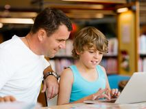 Ragazzino ed suo padre con il computer portatile Fotografia Stock Libera da Diritti