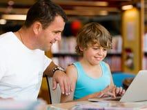 Ragazzino ed suo padre con il computer portatile Fotografie Stock Libere da Diritti