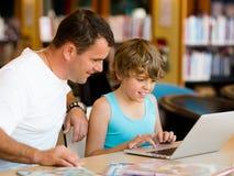 Ragazzino ed suo padre con il computer portatile Immagini Stock