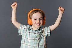 Ragazzino emozionante chegode dell'ascoltare la musica sulle cuffie Fotografia Stock