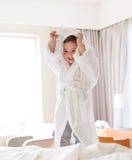 Ragazzino felice in accappatoio sul letto dell'hotel o della casa Fotografie Stock