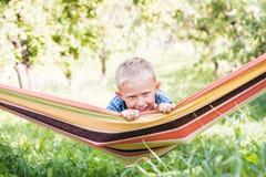 Ragazzino felice in amaca del gioco nel giardino di estate fotografie stock