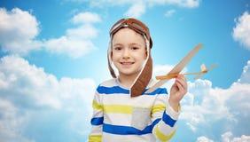 Ragazzino felice in cappello dell'aviatore con l'aeroplano Immagini Stock Libere da Diritti