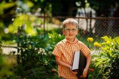 Ragazzino felice del ritratto che tiene un grande libro il suo primo giorno alla scuola o alla scuola materna All'aperto, di nuov Immagini Stock