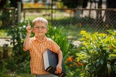 Ragazzino felice del ritratto che tiene un grande libro il suo primo giorno alla scuola o alla scuola materna All'aperto, di nuov Fotografia Stock
