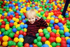 Ragazzino felice divertendosi nel pozzo della palla con le palle variopinte fotografie stock libere da diritti