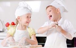 Ragazzino felice e ragazza che cucinano nella cucina Fotografia Stock Libera da Diritti