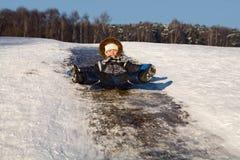 Ragazzino felice su una collina del ghiaccio Fotografia Stock