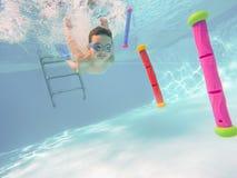 Ragazzino felice subacqueo nel gioco di piscina con i bastoni Immagini Stock Libere da Diritti