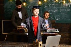 Ragazzino in grandi cappotto del vestito e cappuccio di graduazione Allievo con la madre ed il padre vaghi alla lavagna, famiglia Fotografia Stock