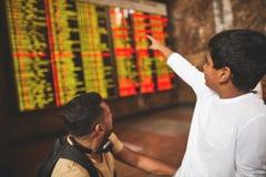 Ragazzino indù piacevole che indica il bordo di partenza immagini stock libere da diritti