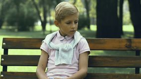 Ragazzino infelice che si siede da solo sul banco in parco, nell'oppressione di scuola e nella crudeltà archivi video