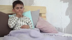 Ragazzino malato che tossisce mentre sedendosi a letto e coprendosi di coperta archivi video