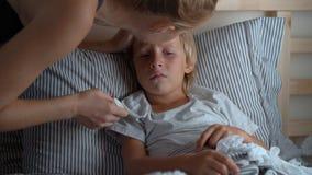 Ragazzino malato in un letto La madre sfrega il petto del ragazzo con l'unguento con gli oli essenziali Concetto di influenza del archivi video