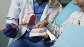 Ragazzino maschio africano di insegnamento del dentista come pulire i denti facendo uso del modello di plastica archivi video