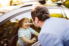 Ragazzino nell'automobile, esaminante dalla finestra suo padre Fotografie Stock