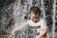Ragazzino nella colonna di acqua della fontana della via immagini stock libere da diritti