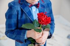 Ragazzino nella condizione del vestito con la rosa rossa, isolata su un fondo leggero fotografia stock