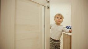Ragazzino in pigiami mentre a casa giocando nascondino con la porta Apre e chiude la porta alla stanza Primo piano video d archivio
