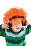 Ragazzino sorridente che ascolta la musica nel headphon Fotografia Stock