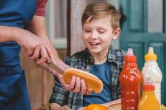 Ragazzino sorridente che esamina il panino di taglio del padre per la cottura del hot dog Immagine Stock Libera da Diritti
