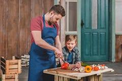 Ragazzino sorridente che esamina le verdure felici di taglio del padre sul tagliere Immagini Stock