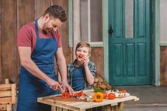 Ragazzino sorridente che esamina le verdure felici di taglio del padre sul tagliere Fotografie Stock Libere da Diritti