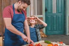 Ragazzino sorridente che esamina le verdure felici di taglio del padre sul tagliere Fotografia Stock