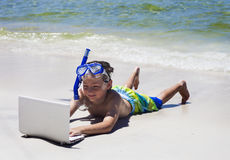 Ragazzino sorridente che per mezzo del computer portatile che si trova sulla spiaggia Fotografie Stock Libere da Diritti
