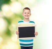 Ragazzino sorridente che tiene lavagna nera in bianco Fotografie Stock