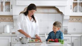 Ragazzino sparato medio che aiuta sua madre mentre cucinando insalata facendo uso della cucina del bordo e del coltello a casa archivi video
