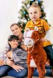 Ragazzino sul cavallo del giocattolo con i suoi genitori sotto l'albero di Chrismas Fotografia Stock