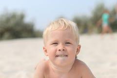 Ragazzino sulla spiaggia, spalmata nella sabbia, sabbia sul suo fronte Immagine Stock