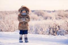Ragazzino sulla strada nevosa di inverno Immagine Stock