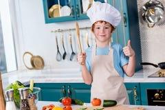 ragazzino sveglio in cappello del cuoco unico e grembiule che sorridono alla macchina fotografica e che mostrano pollice su fotografie stock