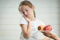 Ragazzino sveglio che aggrotta le sopracciglia sopra il suo pasto mentre giocando con i giocattoli Cattivo comportamento, mangian immagine stock libera da diritti