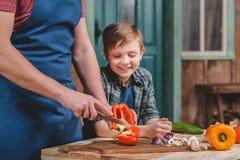 Ragazzino sveglio che esamina le verdure di taglio del padre sul tagliere Fotografia Stock