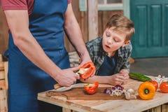 Ragazzino sveglio che esamina le verdure di taglio del padre sul tagliere Immagine Stock Libera da Diritti