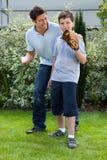 Ragazzino sveglio che gioca baseball con il suo padre Immagini Stock