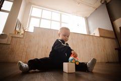 Ragazzino sveglio che gioca con i giocattoli sul pavimento fotografie stock