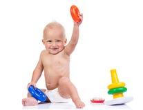 Ragazzino sveglio che gioca con il giocattolo della piramide su bianco Fotografie Stock Libere da Diritti