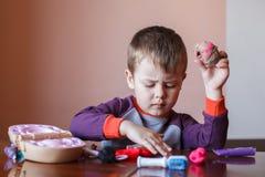 Ragazzino sveglio che gioca con il plasticine multicolore Ragazzo che gioca con gli strumenti dentari dei giocattoli Espressione  immagini stock