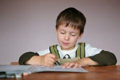 Ragazzino sveglio che impara scrivere Immagini Stock Libere da Diritti